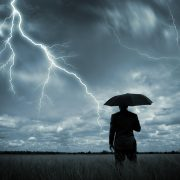 A businessman holding an umbrella in a storm.